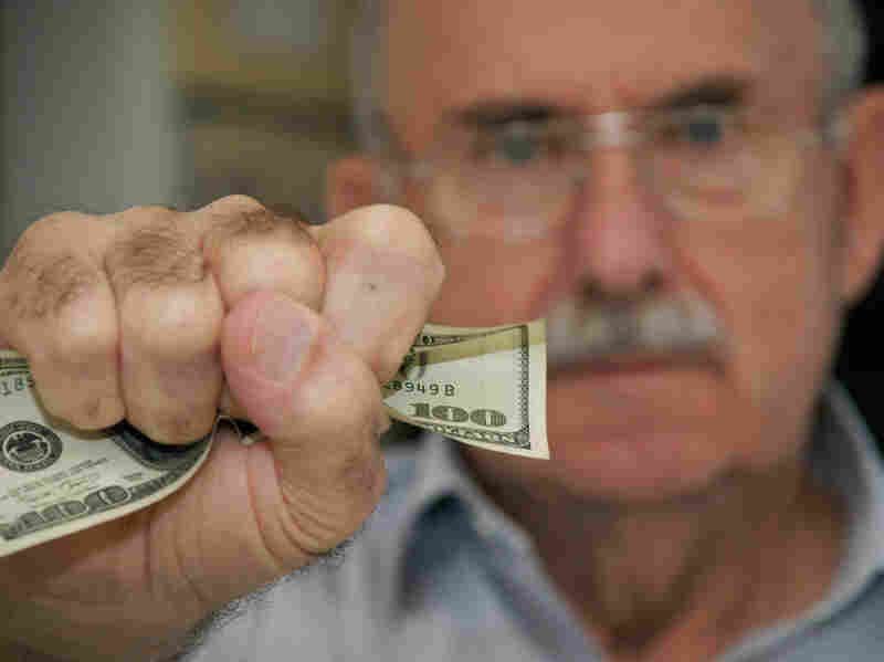 A senior citizen holds a fistful of cash