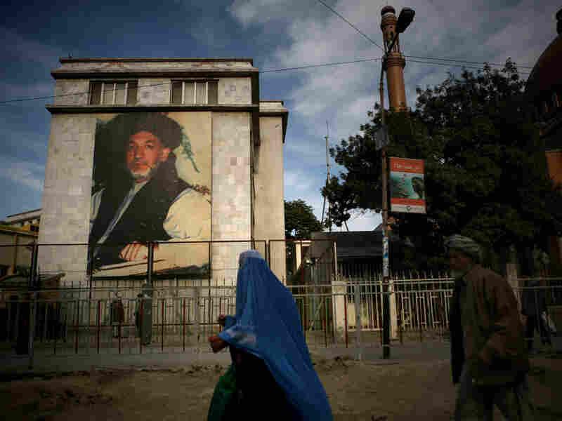 People walk near a huge portrait of Afghan President Hamid Karzai