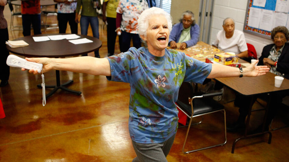 Sofia Henriquez, 76, celebrates after scoring in the Wii bowling competition. In addition to singing and dancing during the game, she cheered on her teammates with a noisemaker crafted from a soda bottle filled with pebbles.