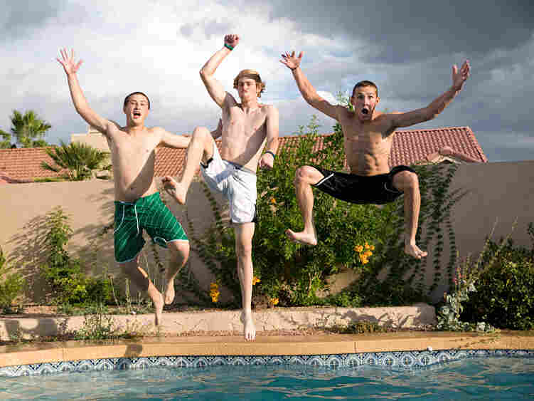 Three young men jump into a pool