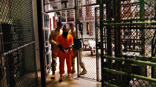 A wide view of a 'noncompliant' detainee escorted by guards at Guantanamo Bay