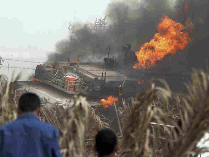 Iraqis look at a burning U.S. Army Abrams battle tank.