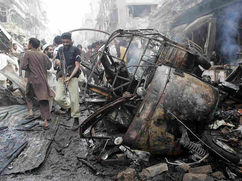 A Pakistani police officer makes his way through wreckage.