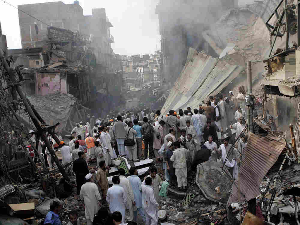 People gather at the site of an explosion in Peshawar.