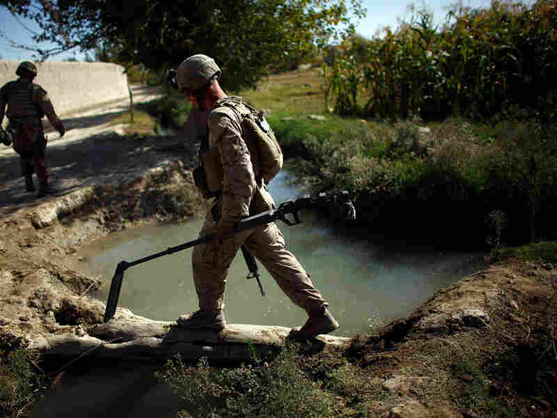A Marine carries a metal detector at the front of his patrol in Helmand province.