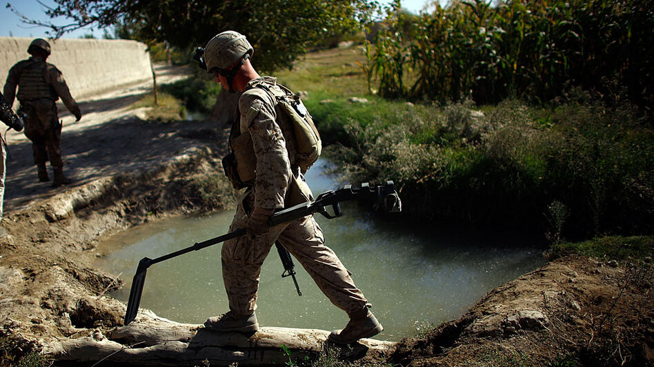 A Marine with with Fox Company of the 2nd Battalion, 8th Marine Regiment carries a metal detector at the front of his patrol in Helmand province in southern Afghanistan near Garmsir.