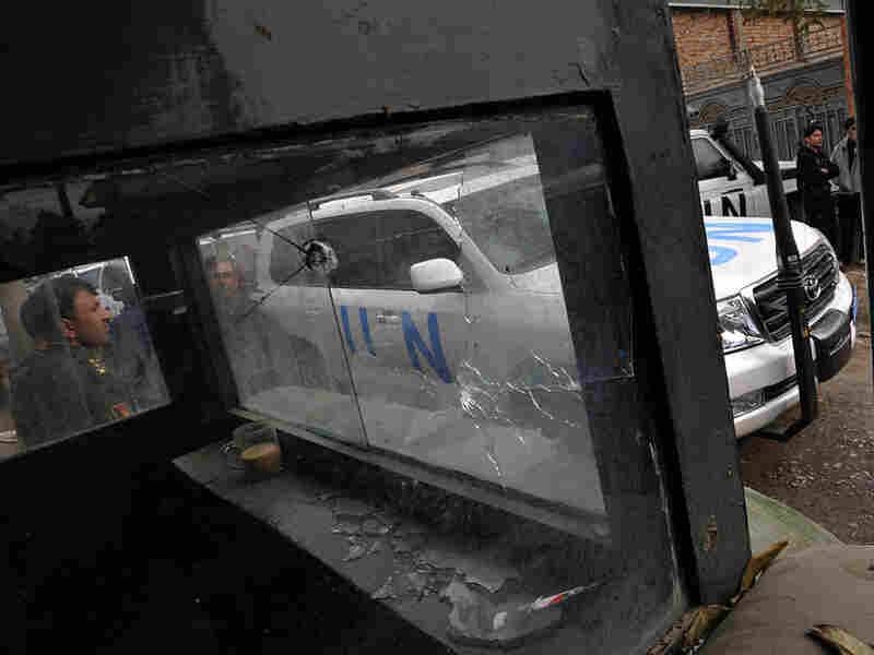 A U.N. vehicle is seen through the bullet-riddled guardhouse of the Bekhtar Guesthouse in Kabul
