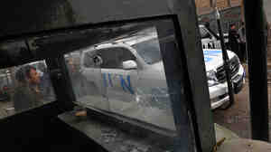 WIDE: A U.N. vehicle seen through the bullet-riddled guardhouse of the Bekhtar Guesthouse in Kabul