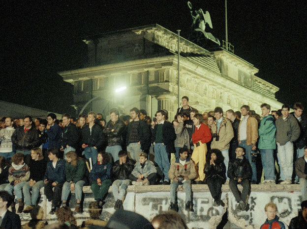 Hundreds of Berliners gather by the Brandenburg Gate to watch the dismantling of the Berlin Wall.