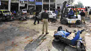 WIDE: Pakistani policemen secure the site of a suicide bomber's blast in Rawalpindi, Pakistan