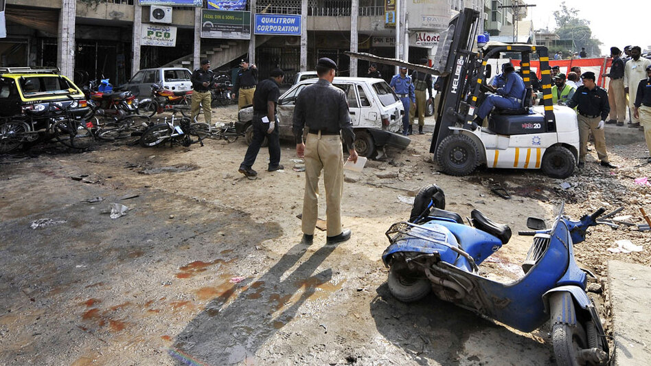Pakistani policemen secure the site of a suicide bomber's blast in Rawalpindi on Monday. A suicide bomber on a motorbike ripped through a line of people outside a bank in the garrison town outside Islamabad, the capital, killing at least 35 people and wounding scores more.
