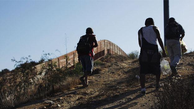 WIDE: Migrants walk next to the U.S.-Mexico border fence in Tijuan