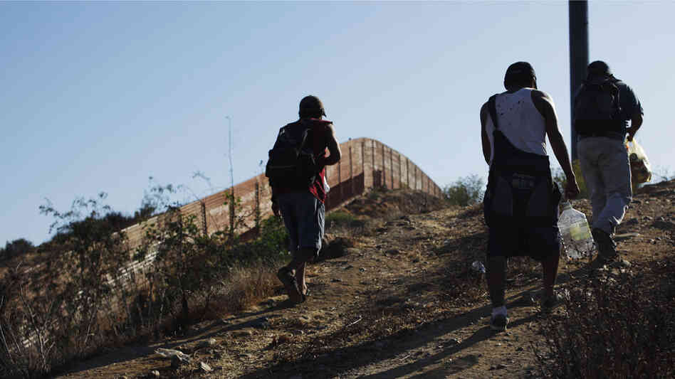 WIDE: Migrants walk next to the U.S.-Mexico border fence in Tij
