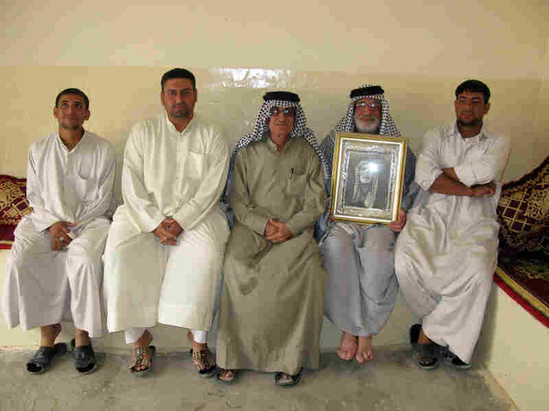 Dakhil Shakir holds a photograph of his father alongside his sons and brother.