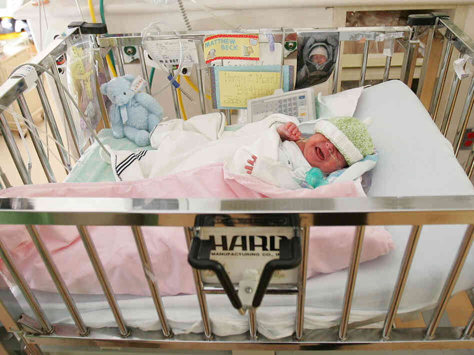 A premature baby lies in an ICU.