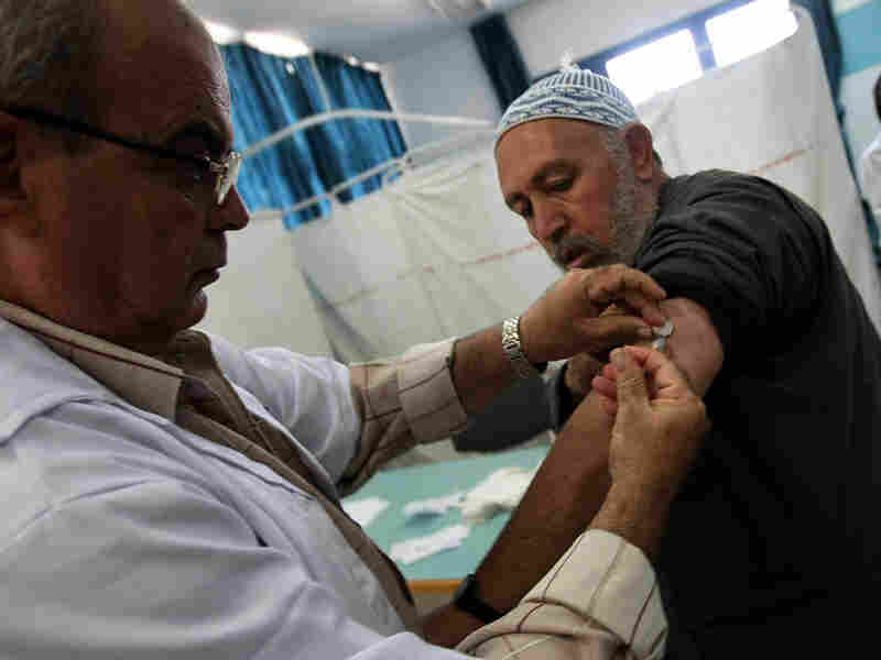 A Palestinian man who has registered to make the hajj gets a flu shot in Gaza City