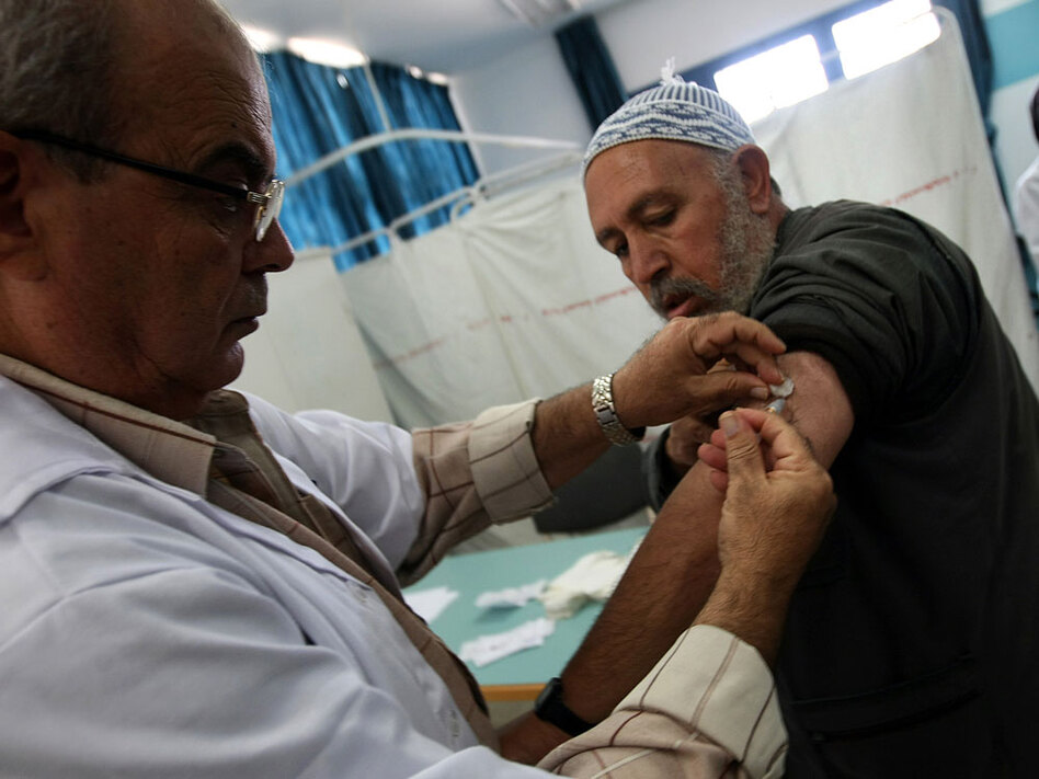 A Palestinian man who has registered to make the hajj gets a flu shot at a medical center in al-Shati refugee camp in Gaza City on Sunday. Saudi Arabian health officials have asked pilgrims to be vaccinated against ordinary and H1N1 flu before making the annual pilgrimage.