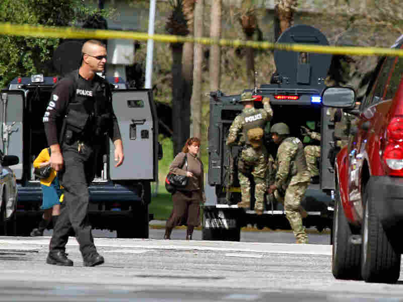 Police and SWAT team members gather at the shooting scene in Orlando. Fla.