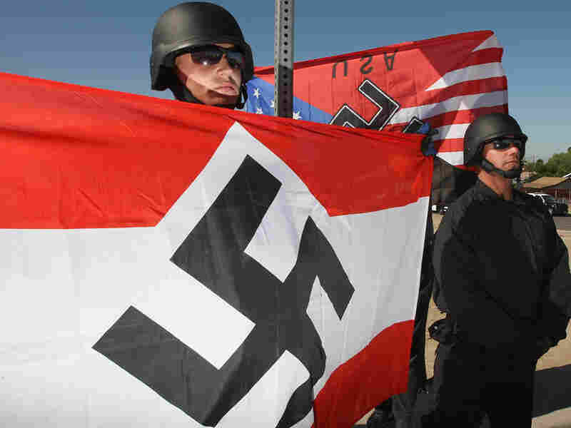 Members of the National Socialist Movement hold swastika flags at a rally.