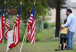 Mourners stand in front of a memorial honoring Fort Hood shooting victims
