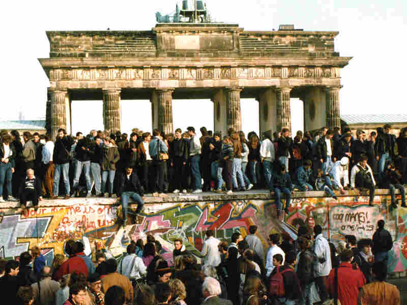 People walk on the Berlin Wall in front of the Brandenburg Gate, on Nov. 10, 1989