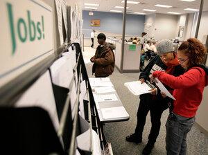 Two women examine jobs listings in Rhode Island