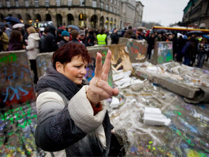 A Polish woman flashes the victory sign near a replica of the destroyed Berlin Wall in Warsaw