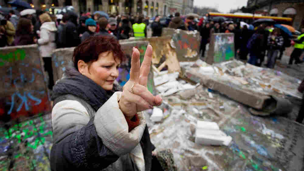 WIDE: A Polish woman flashes the victory sign near a replica of the destroyed Berlin Wall in Warsaw