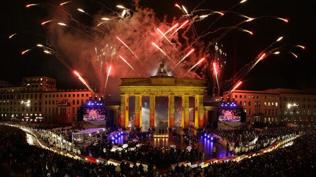 Fireworks explode over Brandenburg Gate in Berlin.