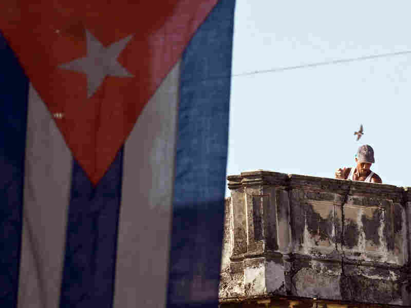 A Cuban works next to a national flag in Havana in August.
