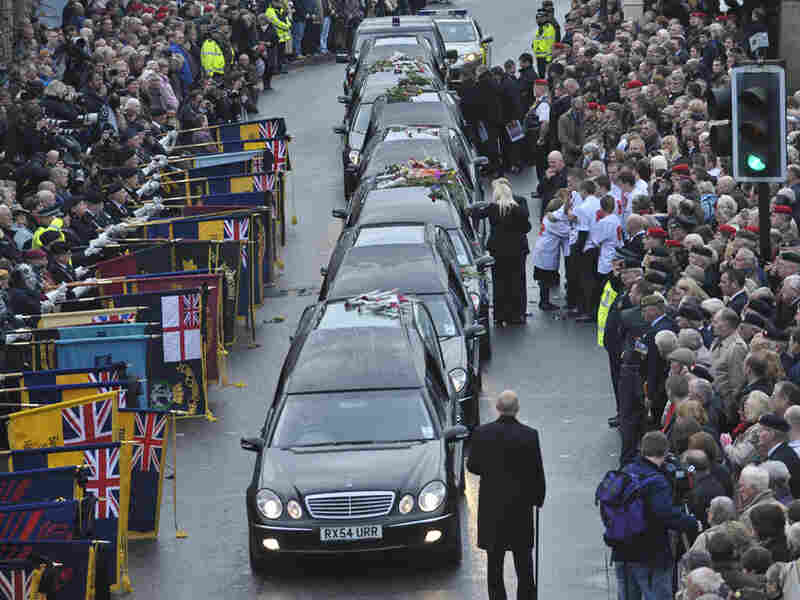 Mourners place flowers on the cortege carrying the coffins of soldiers slain in Afghanistan.