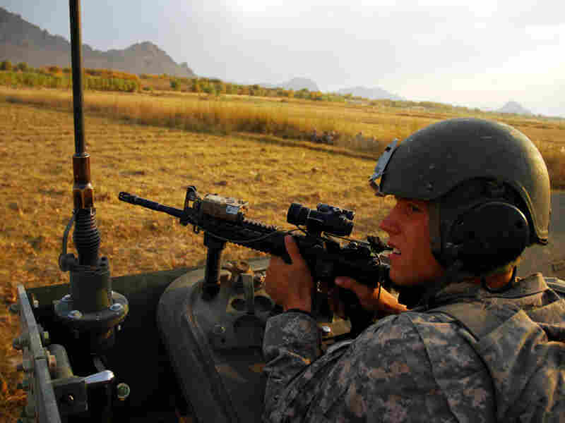Spc. Riley Sheffield looks toward a tree line as insurgents fire on the convoy