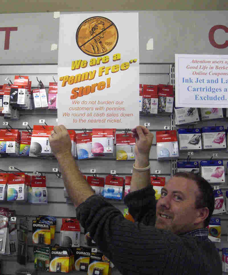 Cashier Andrew Allen stands with his store's 'No Penny' sign.