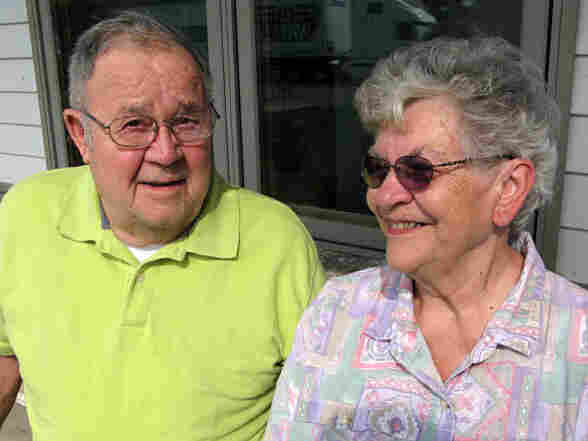 Joe Hauser sits with his wife on their porch.