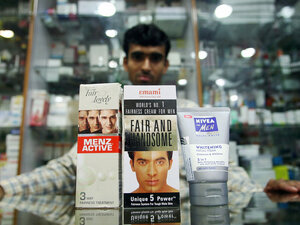 An Indian salesman poses with men's skin fairness products at a shop in New Delhi.