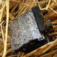 Debris from the burning Stryker is scattered across the field.