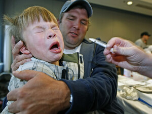 Boy pulls away after receiving H1N1 nasal spray vaccine.