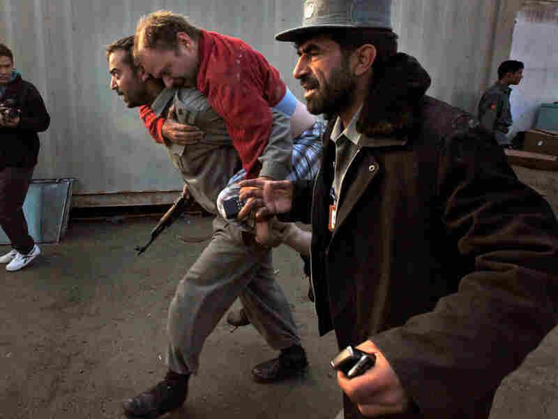 An Afghan policeman carries an injured U.N. worker.