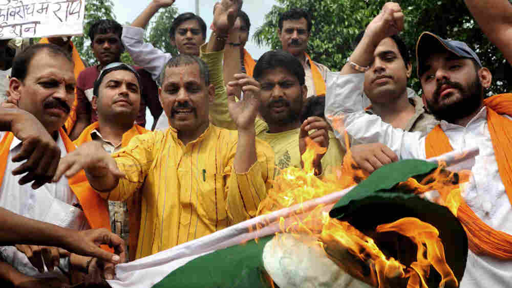 Indian protesters burn a Pakistani national flag