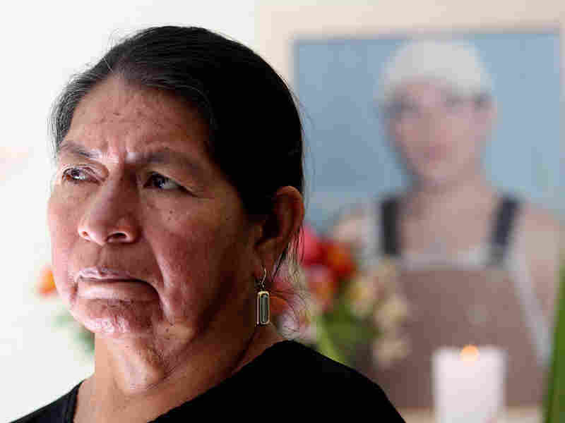 Rosario Lucero poses at her home by a small memorial for her son, Marcelo, in Gualaceo, Ecuador.