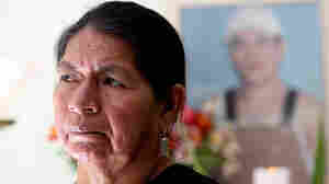 Rosario Lucero poses by small memorial for her son, Marcelo, at her home in Gualaceo, Ecuador. (wide