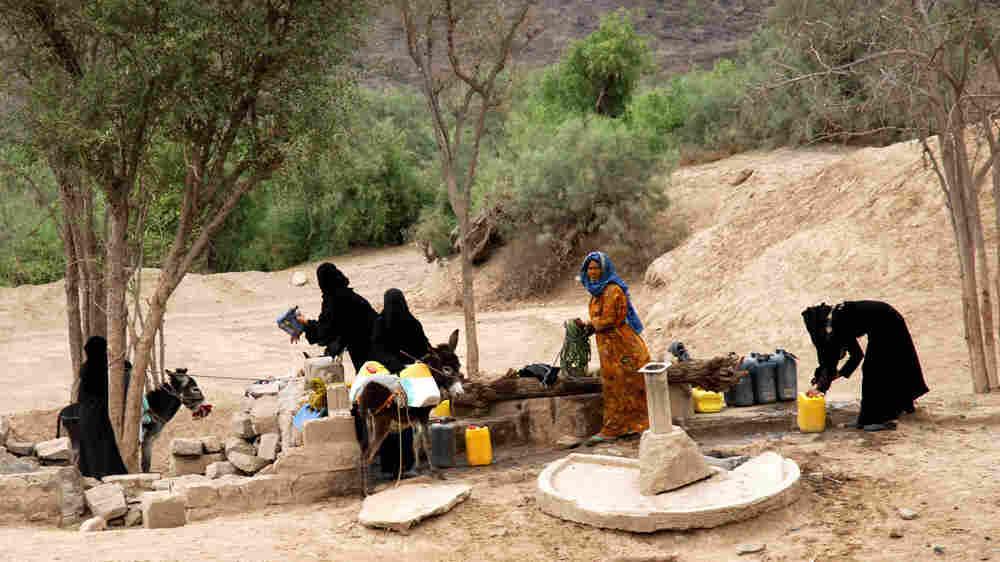 WIDE: Yemeni women gather around a water well south of Sana'a, the Yemeni capital