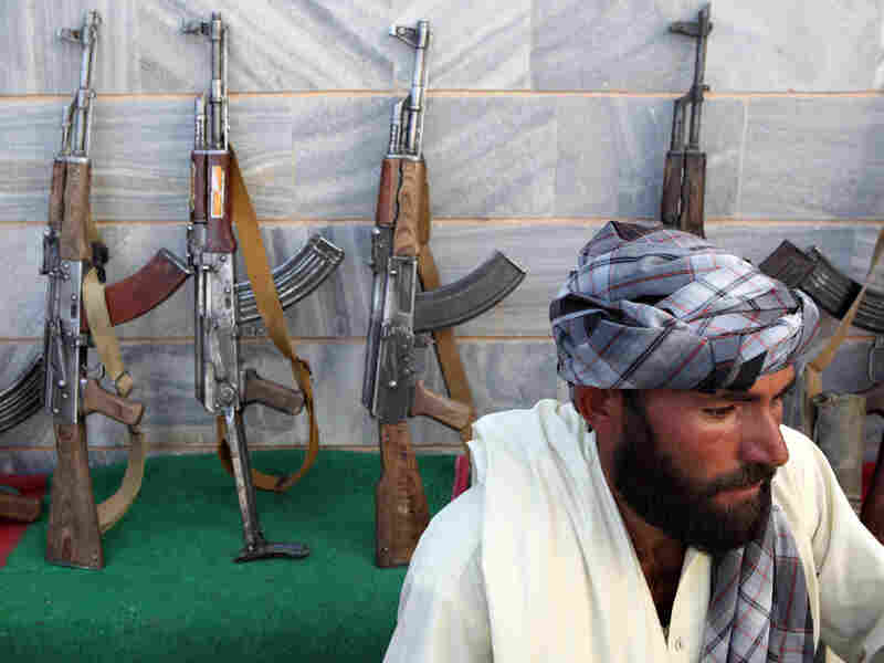 Taliban fighters lay down their weapons