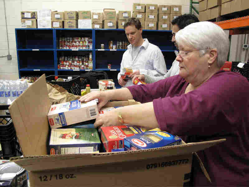 Volunteer Stephanie Durkin packs boxes with food at the Manna Food Center in Rockville, Md.