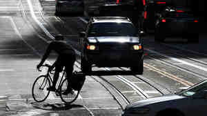 A bicyclist rides down the street in San Francisco.