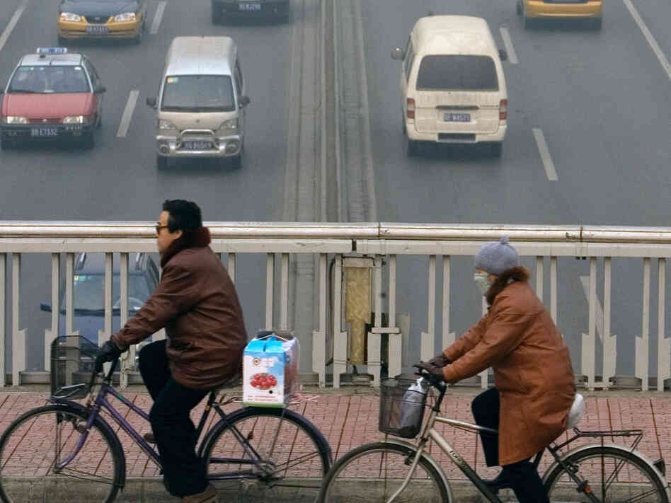 Bicylists riding through smog in Beijing
