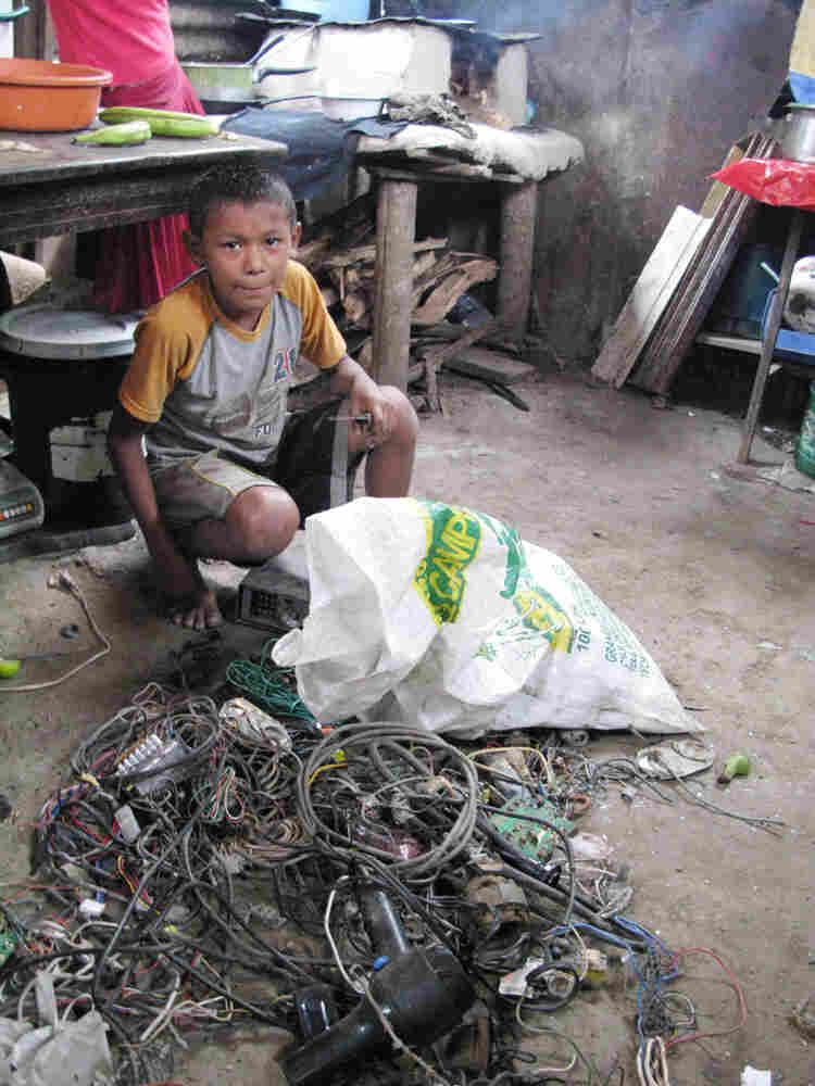 A boy strips insulation off electrical wire; the copper will be sold for scrap