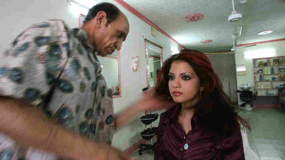 W: A young Iraqi woman has the final touches done to her hair.