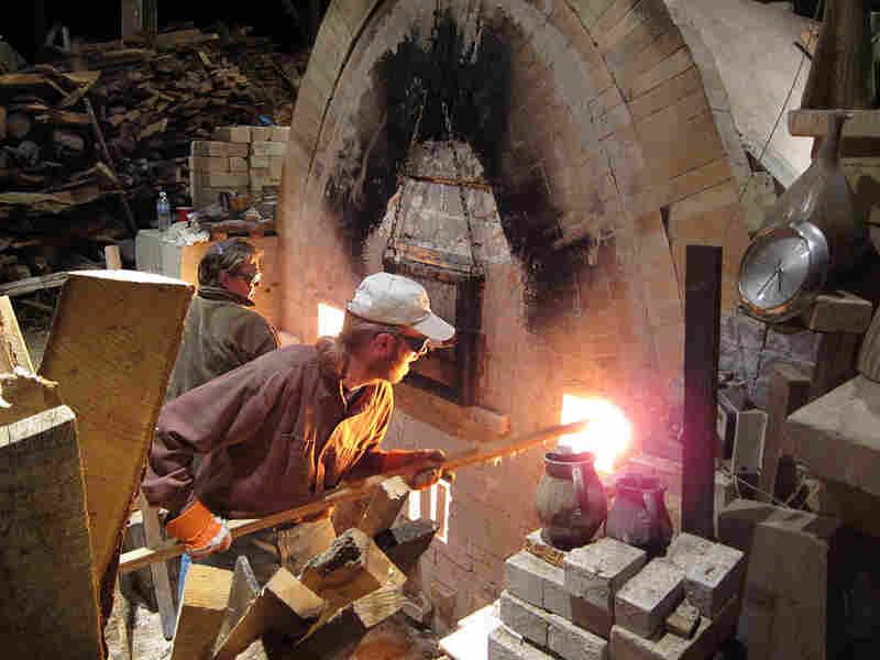 Volunteers Nancy Parent and Dan Corwin-Renner stoke the kiln.