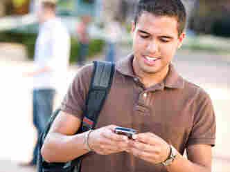 A young Hispanic man checks his mobile phone.